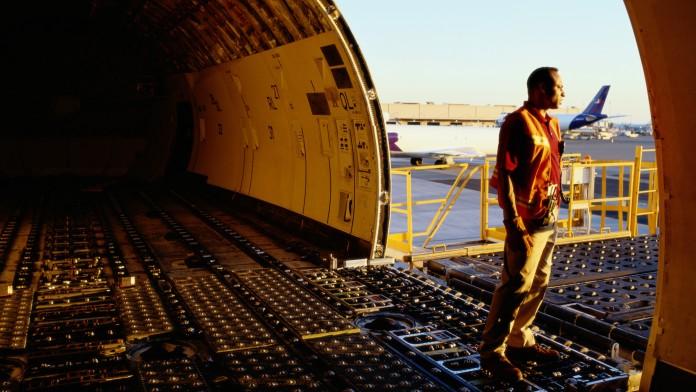 Ein Mann blickt aus einem offenem Cargo Flugzeug, das auf dem Boden steht