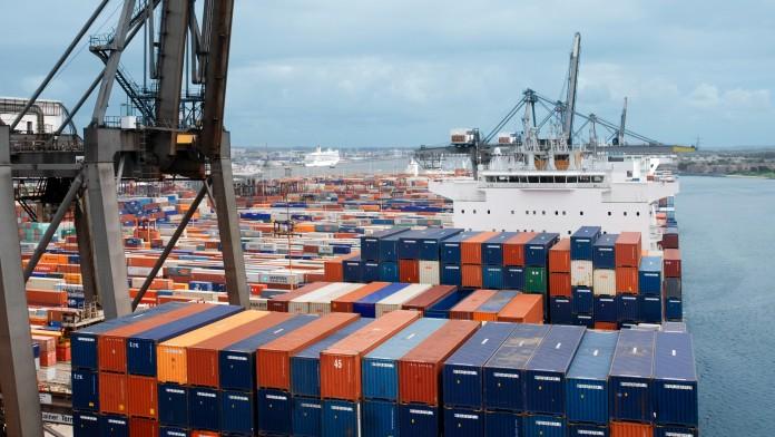 Beladenes Containerschiff im Hafen, daneben ein Verladekran