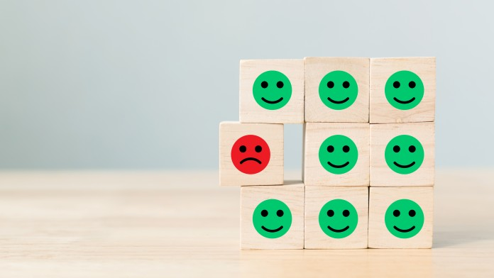 Wooden blocks with icon face emotion happiness in green and sadness in red