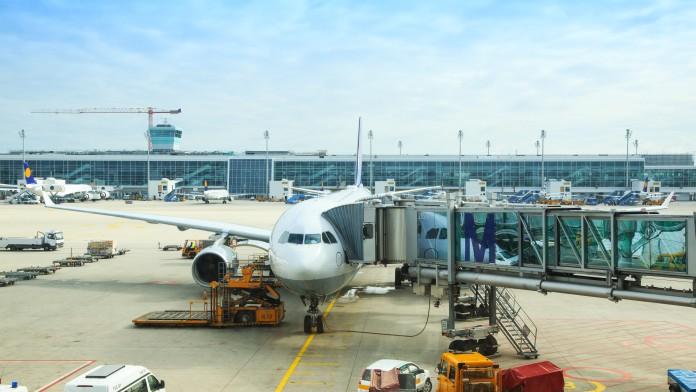 Außenansicht eines sehr belebten Flughafens mit einem Flugzeug im Vordergrund