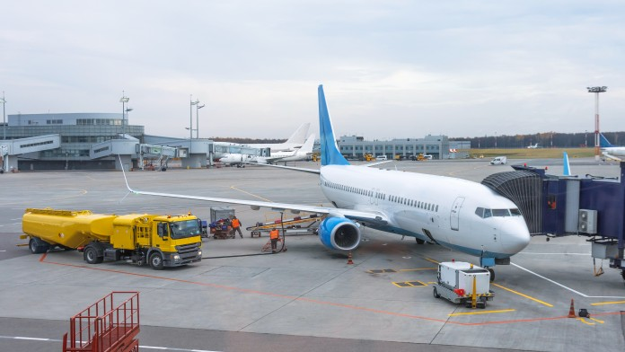 Passenger plane at the telescope of the airport terminal building, for maintenance and refueling before a new flight