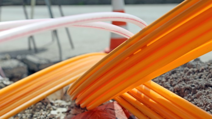 orange cable being layed in the ground