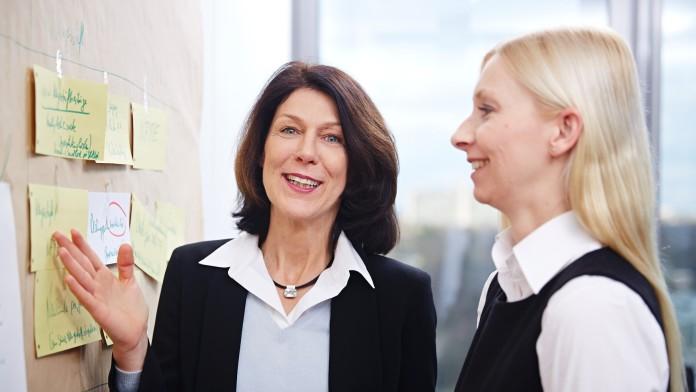 2 Frauen vor Pinnwand