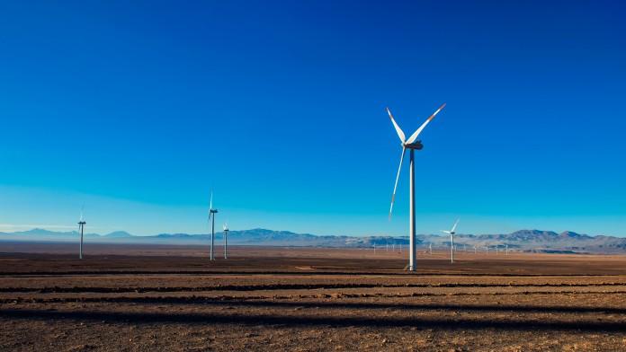 viele Windkaftanlagen an Land vor blauem Himmel
